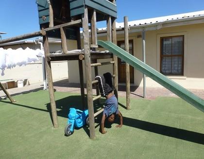 Spelen op een speeltoestel in Vrygrond, Zuid-Afrika
